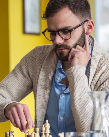 Augenoptiker Jan Büntemeyer als Fotomodell mit Ray-Ban Brille beim Schachspiel